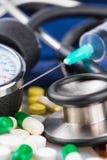 Jeringuilla, diversas píldoras, estetoscopio y sphygmo Foto de archivo