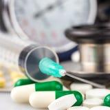 Jeringuilla, diversas píldoras, estetoscopio y sphygmomanometer Imagen de archivo