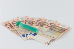 Jeringuilla en cuentas de dinero Imagenes de archivo