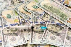 Jeringuilla y dinero - costes del concepto del tratamiento fotografía de archivo libre de regalías