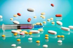 Jeringuilla y diversas píldoras imagen de archivo