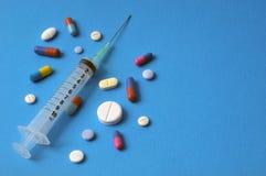 Jeringuilla y drogas en un fondo azul fotografía de archivo