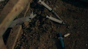 Jeringuillas de drogadictos en el fango metrajes