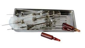 jeringuillas y ampollas de cristal con la medicina en un estetoscopio de la bandeja del metal Imágenes de archivo libres de regalías