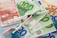 Jeringuillas y dinero euro Fotos de archivo libres de regalías