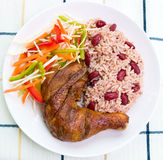 Jerk Chicken with Rice. Caribbean style jerk chicken served with rice mixed with red kidney beans. Dish accompanied with vegetable salad. Shallow DOF Stock Image