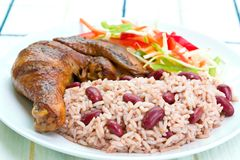 Jerk Chicken with Rice. Caribbean style jerk chicken served with rice mixed with red kidney beans. Dish accompanied with vegetable salad. Shallow DOF on the rice Stock Images