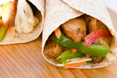 Jerk Chicken Wrap. Caribbean style wrap stuffed with jerk chicken, sweet pepper and cabbage. Shallow DOF Royalty Free Stock Photography