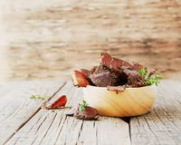 Jerked meat, cow, deer, wild beast or biltong in wooden bowls on a rustic table, selective focus. Jerked dried meat, cow, deer, wild beast or biltong in wooden Royalty Free Stock Photos