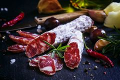 Jerked Italian salami with rosemary, spices, olives and oil. Dar. K vintage background, low key, selective focus royalty free stock image