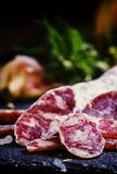 Jerked Italian salami with rosemary, spices, olives and oil. Dar. K vintage background, low key, selective focus royalty free stock images
