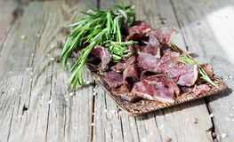 Jerked meat, cow, deer, wild beast or biltong in wooden bowls on a rustic table, selective focus. Jerked dried meat, cow, deer, wild beast or biltong in wooden Stock Image