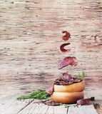 Jerked meat, cow, deer, wild beast or biltong in wooden bowls on a rustic table, selective focus. Jerked dried meat, cow, deer, wild beast or biltong in wooden Stock Photo
