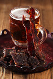 Jerky beef with beer - homemade dried cured spiced meat Royalty Free Stock Photos