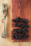 Jerky beef - homemade dry cured spiced meat. Top view Royalty Free Stock Photos
