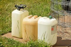 Jerry can. Three old plastic cans in the grass Royalty Free Stock Photography