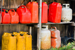Jerry Cans and Propane Tanks. A group of jerry cans and propane tanks sit on shelves in a wooden shed Royalty Free Stock Photo