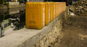 Jerry cans stands in a row near dirty river photo taken in Jakarta Indonesia. Java Stock Image