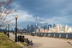 Jersey City, NJ/США - март 2016: город Нью-Йорка как увидено от парка штата свободы на дне весны пасмурном стоковые фото