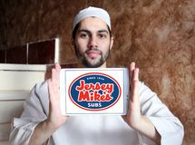 Jersey Mike`s Subs fast food chain logo. Logo of Jersey Mike`s Subs restaurant on samsung tablet holded by arab muslim man. Jersey Mike`s Subs is an American stock photography