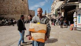 JERUSALÉM, ISRAEL - 10 DE FEVEREIRO DE 2015: O vendedor das frutas e legumes leva caixas em sua loja no bazar do video estoque