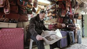 JERUSALÉM, ISRAEL - 10 DE FEVEREIRO DE 2015: O vendedor ensaca a leitura de um jornal na cidade velha do bazar árabe do Jerusalém vídeos de arquivo