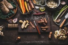 Jerusalem artichoke peeling preparation on rustic kitchen table with pot, diced vegetables, oil and ingredients, top view. Healthy. And clean seasonal food stock image