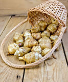 Jerusalem artichokes with basket on board Royalty Free Stock Photos