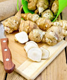 Jerusalem artichokes cut with knife and bucket on board Stock Image