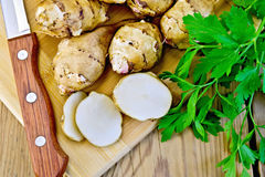 Jerusalem artichokes cut with knife and parsley Royalty Free Stock Images