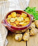 Jerusalem artichokes fried in a pan on the board Royalty Free Stock Photo