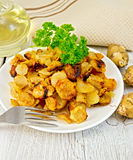 Jerusalem artichokes fried with parsley on plate Royalty Free Stock Image