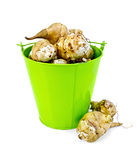 Jerusalem artichokes in a green bucket and on the table Stock Photos