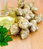 Jerusalem artichokes with oil and parsley on board Royalty Free Stock Photo
