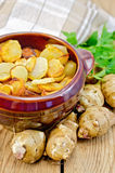 Jerusalem artichokes roasted in a clay pot on a board Royalty Free Stock Photos