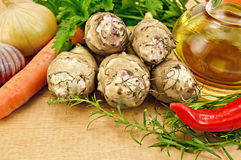 Jerusalem artichokes with vegetables on the board Stock Image