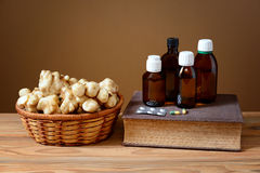 Jerusalem artichokes in wicker baskets, books and medicines Royalty Free Stock Photos
