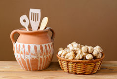 Jerusalem artichokes in wicker baskets with wooden kitchen utensils Royalty Free Stock Image