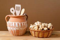 Jerusalem artichokes in wicker baskets with wooden kitchen utensils. In a ceramic pot Royalty Free Stock Image