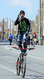 Jerusalem Daredevil. A stuntman riding his bike by standing on top of his seat, hands free on Jaffa Street in Jerusalem,Israel Royalty Free Stock Image