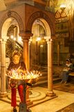 JERUSALEM, ISRAEL - April 2, 2018: woman sets candles in the Church of the Holy Sepulchre. royalty free stock images