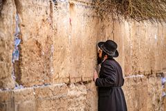 11/23/2018 Jerusalem, Israel, Believing is praying near the wall of crying in a big black hat. And kiss the wall stock photo