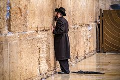 11/23/2018 Jerusalem, Israel, Believing is praying near the wall of crying in a big black hat. And kiss the wall stock photos