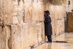 11/23/2018 Jerusalem, Israel, Believing is praying near the wall of crying in a big black hat. And kiss the wall stock photography