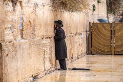 11/23/2018 Jerusalem, Israel, Believing is praying near the wall of crying in a big black hat. And kiss the wall stock images
