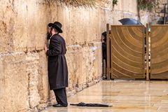 11/23/2018 Jerusalem, Israel, Believing is praying near the wall of crying in a big black hat. And kiss the wall royalty free stock photo