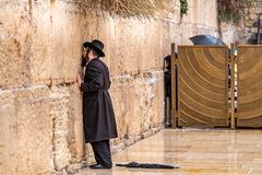 11/23/2018 Jerusalem, Israel, Believing is praying near the wall of crying in a big black hat. And kiss the wall royalty free stock photos