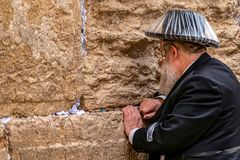 11/23/2018 Jerusalem, Israel, Believing is praying near the wall of crying in a big black hat in a raincover. Under the rain stock photos