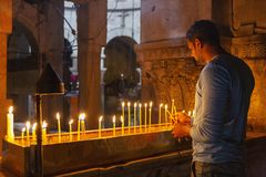 Jerusalem, Israel, 09/11/2016: A believing man puts candles and prays in the temple of the Holy Sepulcher royalty free stock photo