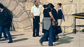 Black dress Jewish men. Jerusalem, Israel - Circa 1981: Senior Jewish men in typical black dress and hat walking in Old City of Jerusalem, Western Wall Plaza stock footage